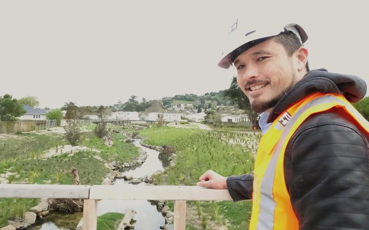 Man in hi vis vest stands on bridge looking at replanted stream