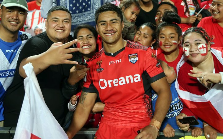Tongan scrumhalf, Ata Hingano, poses with fans after playing a pivotal part in victory over Samoa