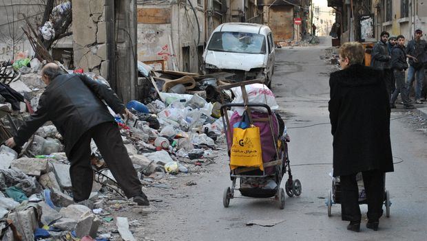 A man looking for items to scavenge amid debris and garbage in a street in a rebel area of Homs.