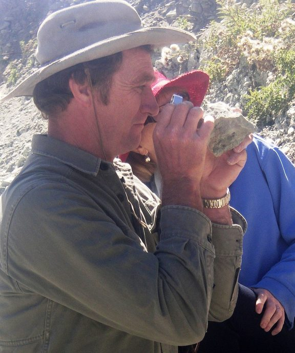 Trevor Worthy inspects a small animal bone embedded in a piece of rock.