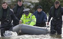 Royal Engineers transport a policeman by boat through floodwaters in Thames Meadow, near Shepperton, south of London.