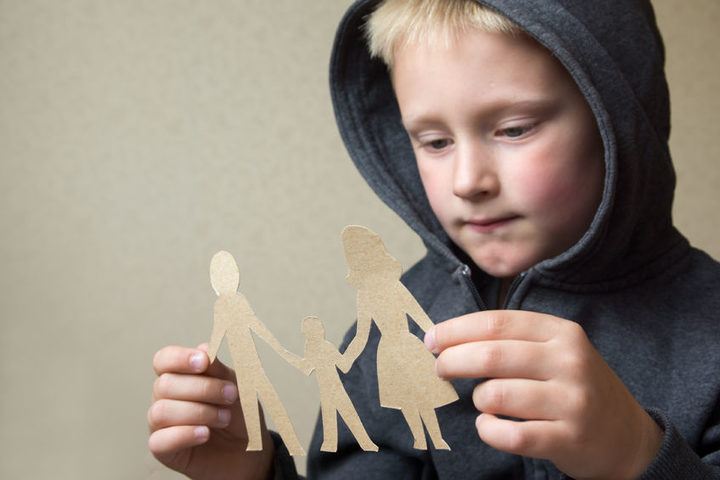 A photo of a boy with a paper cut out family holding hands