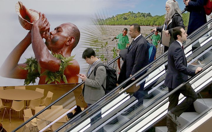 Visitors use an escalator past a poster featuring the Fiji Islands on the opening day of the COP 23 United Nations Climate Change Conference on November 6, 2017 in Bonn, Germany.