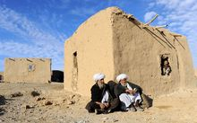 Afghan residents sit outside a hut on the outskirts of Herat.