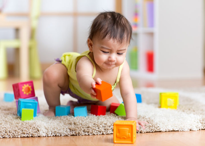 A photo of a toddler playing with blocks