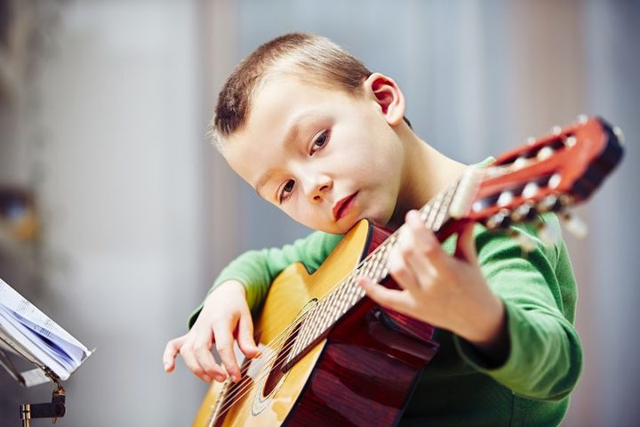 A photo of a little boy playing the guitar at home