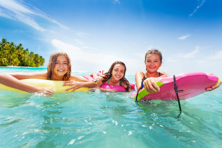A photo of three girls swimming in the sea on surfboards