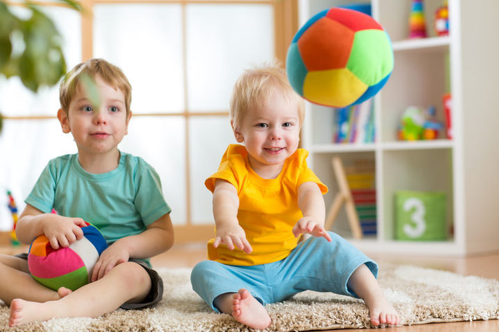 A photo of two toddlers playing with balls