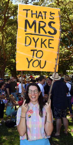 "A woman holds a banner as supporters of the same-sex marriage ""Yes"" vote gather to celebrate the announcement in a Sydney park."