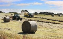 Two tractors and hay bales.