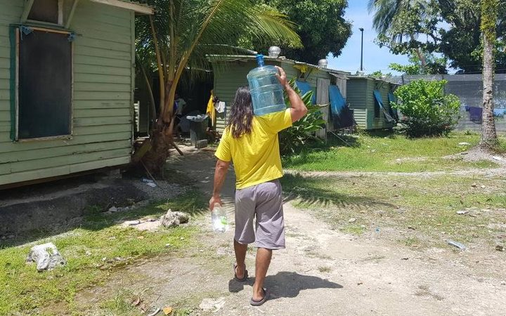 A refugee carries well water in the Manus Island detention centre.