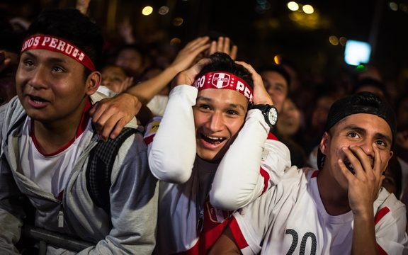 Peruvian football fans celebrate as they watch their team's 2018 World Cup football qualifier match against New Zeland on a big screen at a park in Lima, on November 10, 2017.