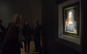 Visitors view the painting 'Salvator Mundi' by Leonardo da Vinci at Christie's New York Auction House.