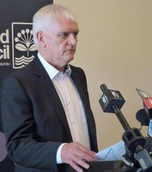 Doug McKay announcing the findings of the review in December 2013.