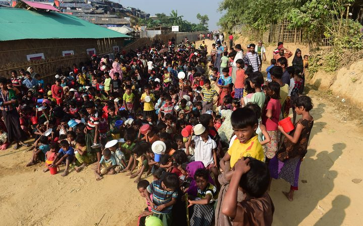 Rohingya refugee children wait for food at a food distribution center in Thankhali refugee camp in the Bangladeshi district of Ukhia.