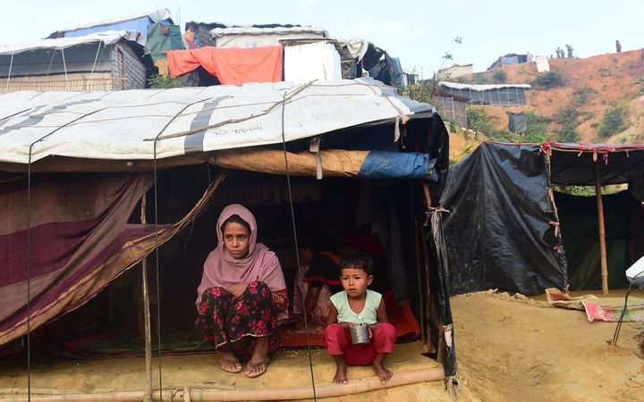 Rohingya refugees sit in front of their makeshift shelter