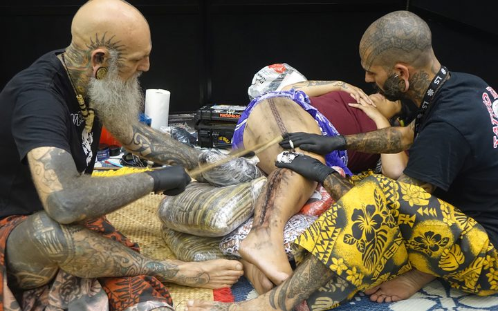 Former Auckland tattooist Brent McCown, (left) and his colleague Smiley Dogg, from Mallorca, create a tattoo using traditional Samoan techniques at the NZ Tattoo and Art Festival in New Plymouth.