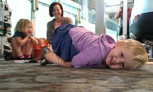 Zoe Psirides (front), Lilly Psirides and mum Sally Huford waiting at the airport on Thursday.