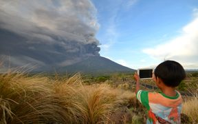 A boy takes pictures during Mount Agung's eruption.
