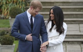 Britain's Prince Harry stands with his fiancée US actress Meghan Markle as she shows off her engagement ring at Kensington Palace in west London.