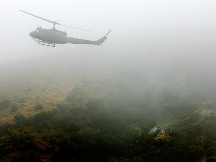 An Air Force Iroquois hovers above the crash site.
