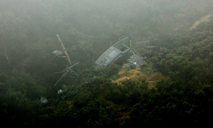 The wreckage of NZ3806 on the side of the ravine. The helicopter is lying on its right hand side, has broken in two and slightly covered by mist.