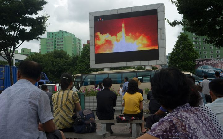 People watching as coverage of an earlier ICBM missile test is displayed on a screen in a public square in Pyongyang in July.