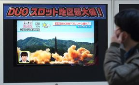 A pedestrian walks in front of a television screen displaying file news footage of a North Korean missile launch, in Tokyo, on Wednesday.