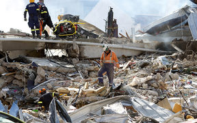 Rescuers search through the ruins of the collapsed CTV building