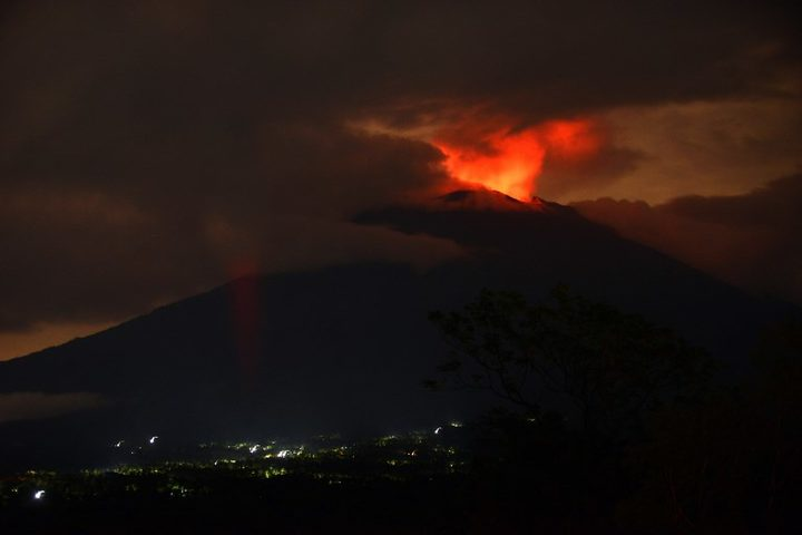 A pre-dawn view shows the erupting Mount Agung volcano.