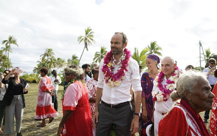 French Prime Minister Edouard Philippe reacts after receiving a flower neklace during a welcoming ceremony at the Tiga chiefdom, on Tiga island on December 3, 2017. / AFP PHOTO / Fred Payet