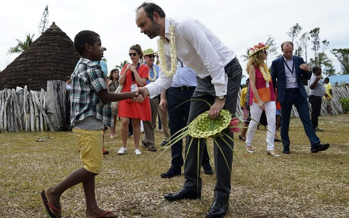 French Prime Minister Edouard Philippe (R), shakes hands with a child during welcoming ceremony at the Grande Case in the district of Wetr, in Hnatalo, on the Lifou Island, during his visit to the French overseas territory of New Caledonia on December 3, 2017. / AFP PHOTO / Fred Payet