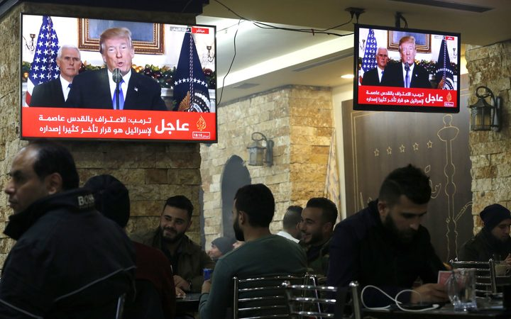 Palestinians in a cafe in the West Bank city of Ramallah as TV screens show US President Donald Trump announcing the recognition of the disputed city of Jerusalem as Israel's capital.