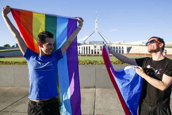 Equality ambassadors and volunteers from the Equality Campaign celebrate as they gather in front of Parliament House in Canberra.