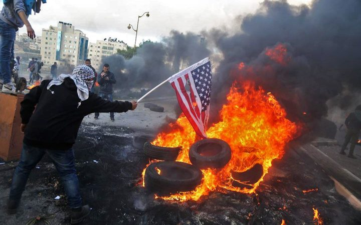 A Palestinian protester sets alight an America flag during clashes with Israeli troops at a protest against US President Donald Trump's decision to recognize Jerusalem as the capital of Israel.