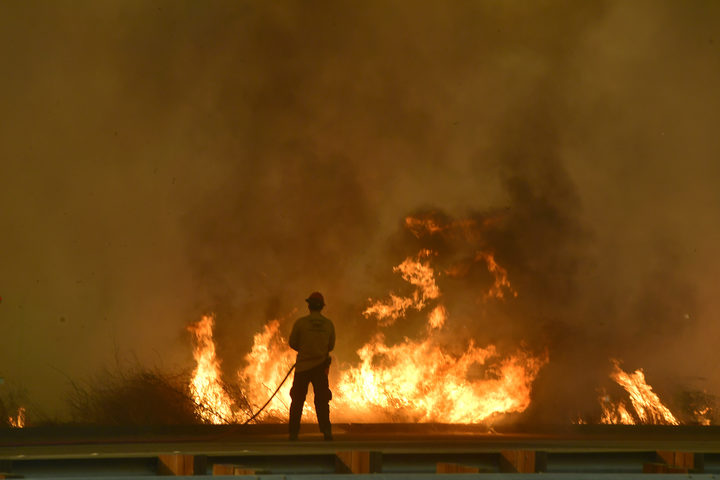 A firefighter battles flames near the US 101 highway in Ventura County.
