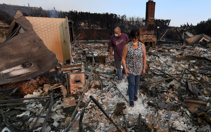John and Julie Wilson sort through the remnants of their burnt out home after the Thomas wildfire swept through Ventura, California.