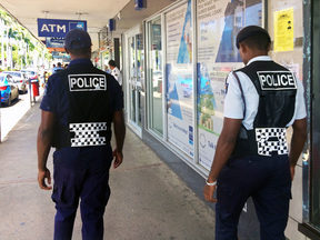 70710201 - lautoka, fiji -  dec 30 2016:fijian police officers patrolling in the main street. the fiji police force annual statistics reveal an 18% increase in crime cases in 2015.