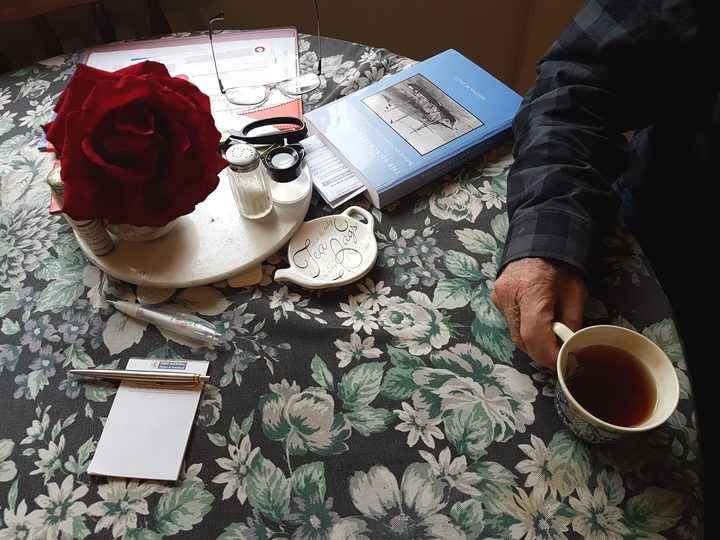 A photo of Baden Norris's kitchen table with book glasses, flowers and a cup of tea