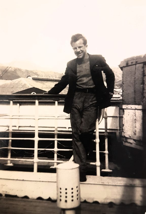 A photo of Baden Norris in front of a tug boat at Lyttleton