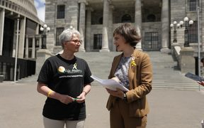 Corinda Taylor presents a petition with 55,000 signatures to Chlöe Swarbrick on the steps of parliament