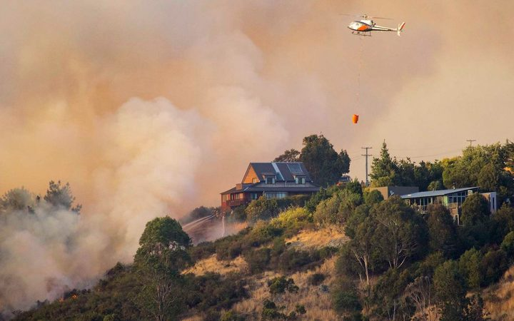 Firefighters try to save a house from fire on Port Hills in Christchurch. The fires destroyed nine houses and one helicopter pilot died fighting the blaze.