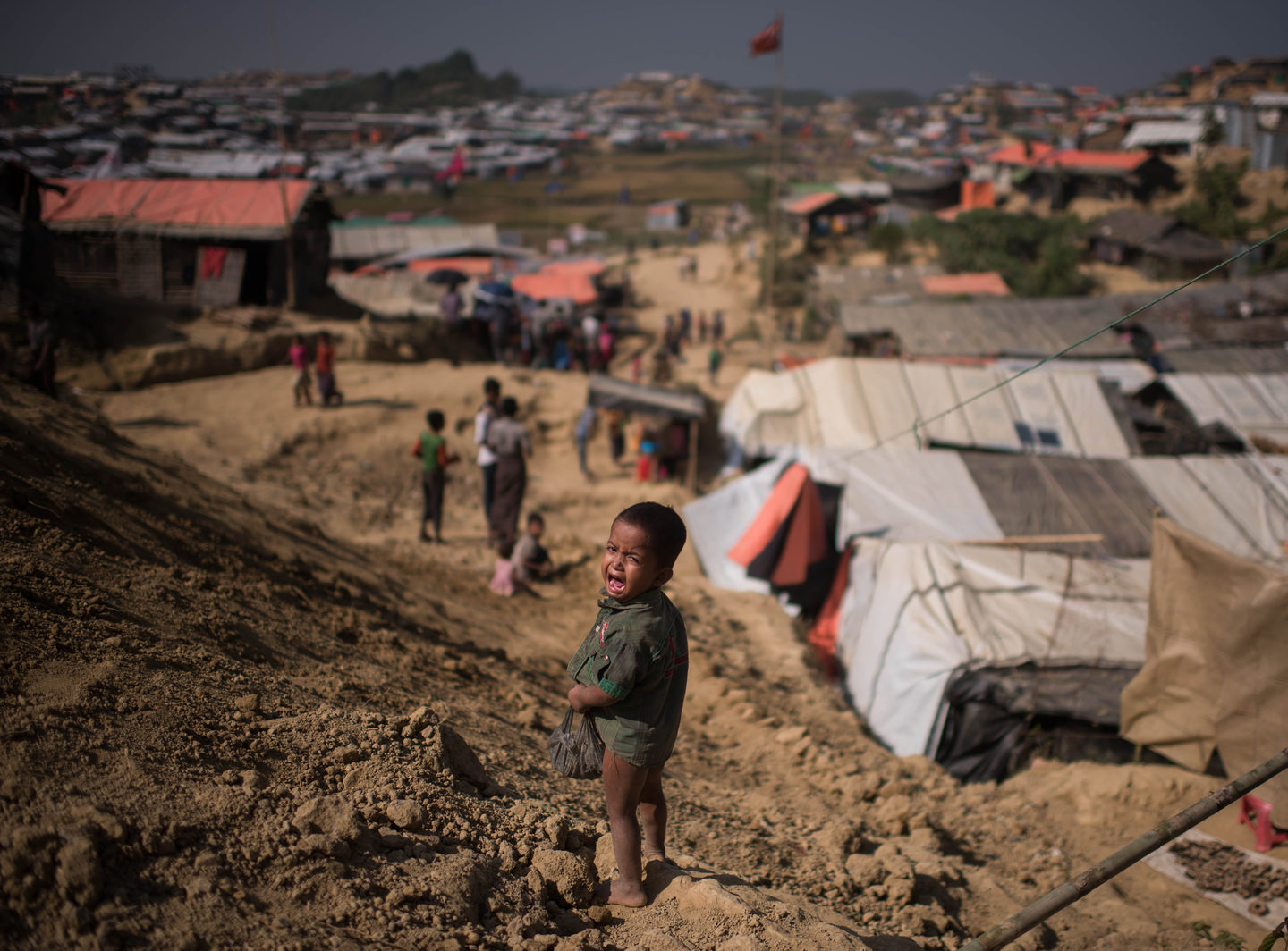 A Rohingya Muslim refugee child cries as he stands near the Thyangkhali refugee camp at Cox's Bazar on November 29, 2017.