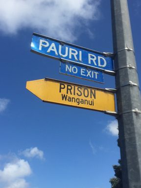 "An image of a road sign pointing to Whanganui prison, with another sign beneath that reads ""no exit."""