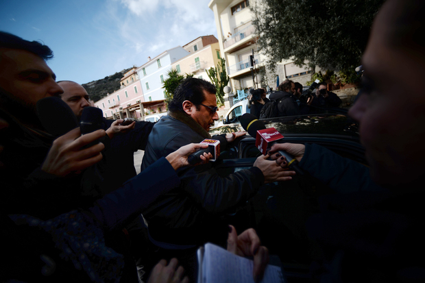 The Costa Concordia captain is surrounded by media as he arrives back at Giglio Island.