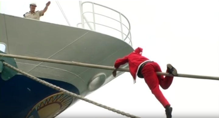 Halfway up the mooring rope, a Santa is refused entry to the ship by a uniformed guard.