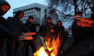 Pro-Russian demonstrators warm themselves near a bonfire as they rally near Crimean parliament building.