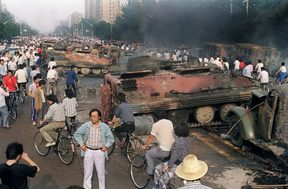 A file photo taken on 4 June, 1989 shows Beijing residents gathering around the smoking remains of over 20 armoured personnel carriers burnt by demonstrators during clashes with soldiers near Tiananmen Square.
