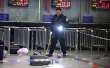 A Chinese police investigator inspects the scene of the attack.
