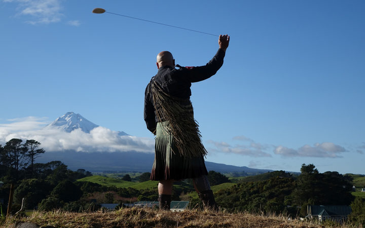 Rangi Kipa swings a purerehua (Māori musical instrument) at the Taranaki settlement of Parihaka ahead of the Crown's formal apology for the military invasion of 1881.